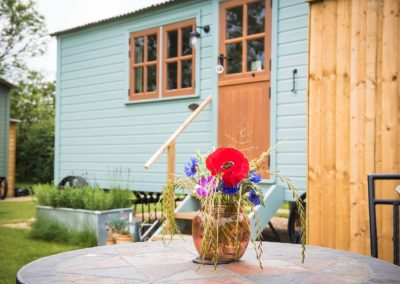 Morndyke Shepherds Huts Exterior with Table and Flower Vase